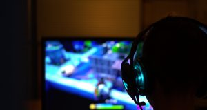 Gracz siedzący przed komputerem, na ekranie widoczna jest rozgrywka, gracz ma na uszach słuchawki