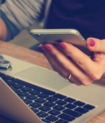 laptop uzyskany poprzez wypożyczenie laptopa leży na biurku, przy którym siedzi kobieta, która trzyma w ręku telefon