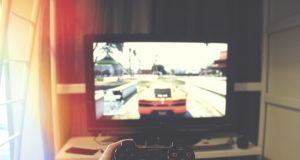 Człowiek grający na konsoli, na ekranie widać rozgrywkę; ujęcie z pierwszej osoby; w ręku jest kontroler